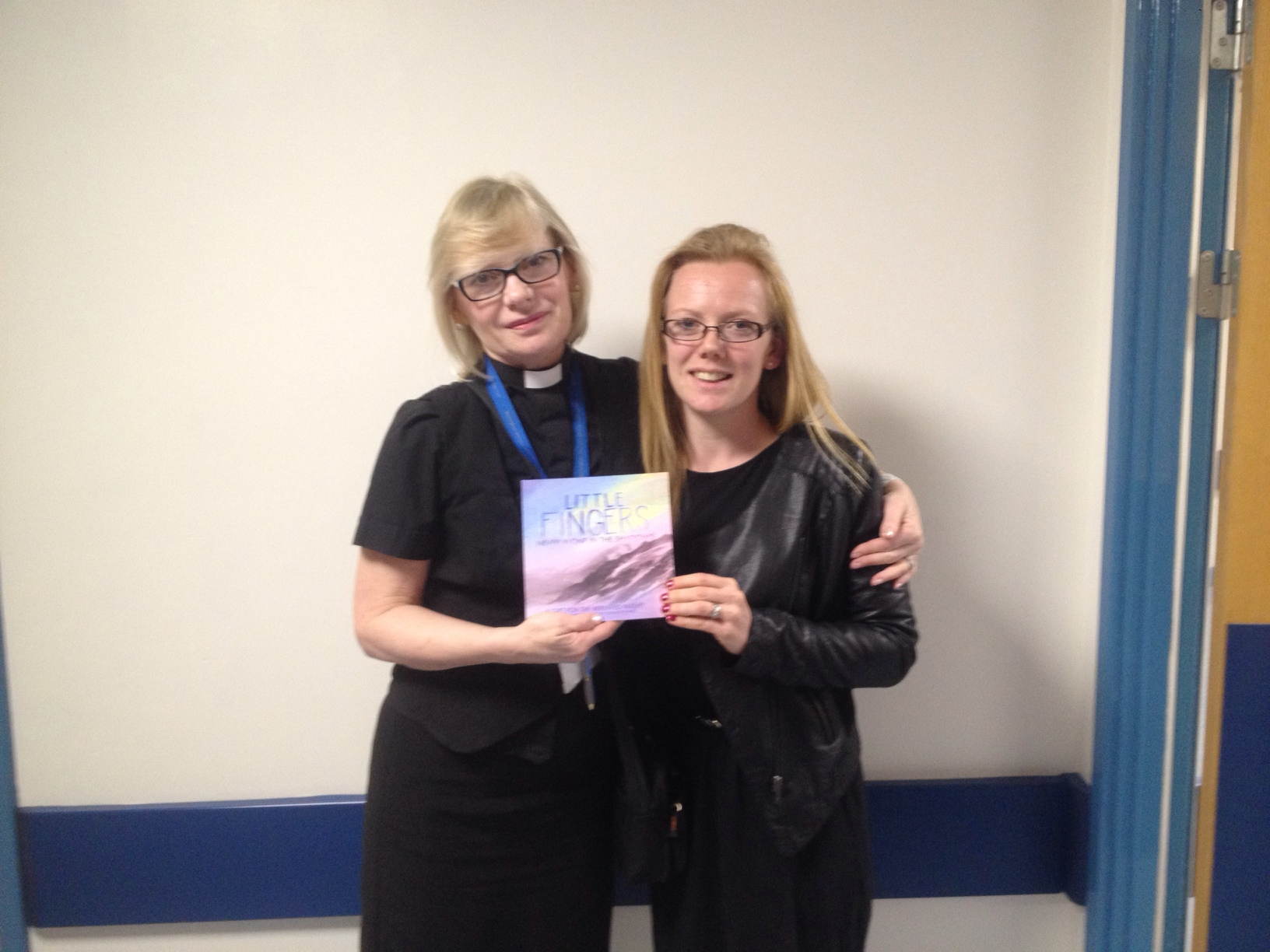Picture of Charlotte handing Little Fingers books over to denise